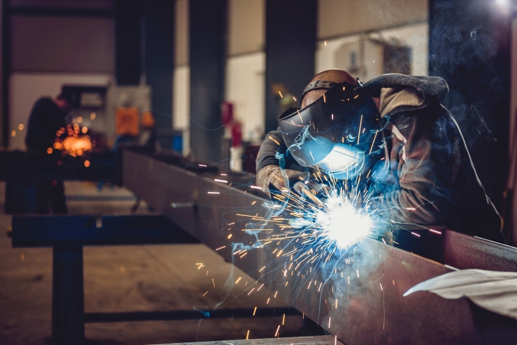 person doing welding on a large steel fabrication beam