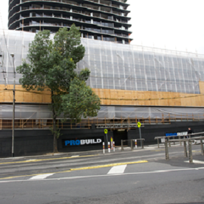 view of outside of building covered in scaffold